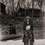 This picture is from 1926. It shows Louise Calfee (later Johannaber) with Bill. Grandpa Bublitz is sitting in his dugout canoe which he made. He also made canes of diamond willow and willow furniture which adorned the beach for years. Notice the screened porch on the main house.