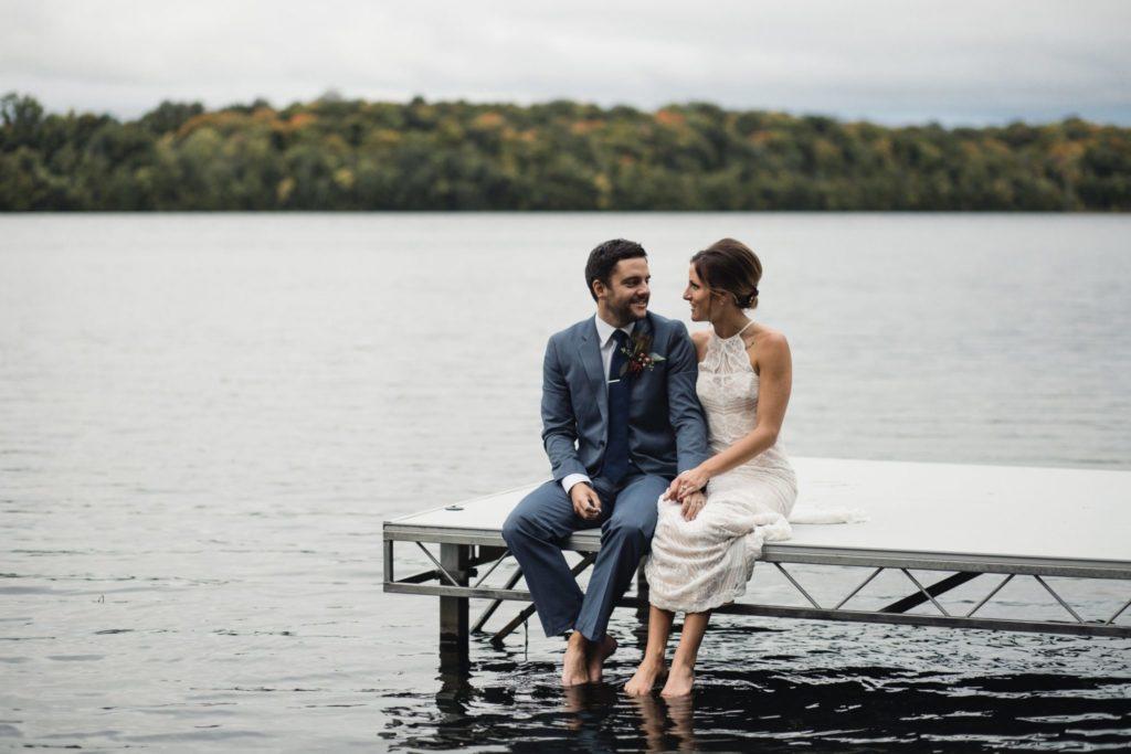 Bride and Groom Sitting on Resort Dock