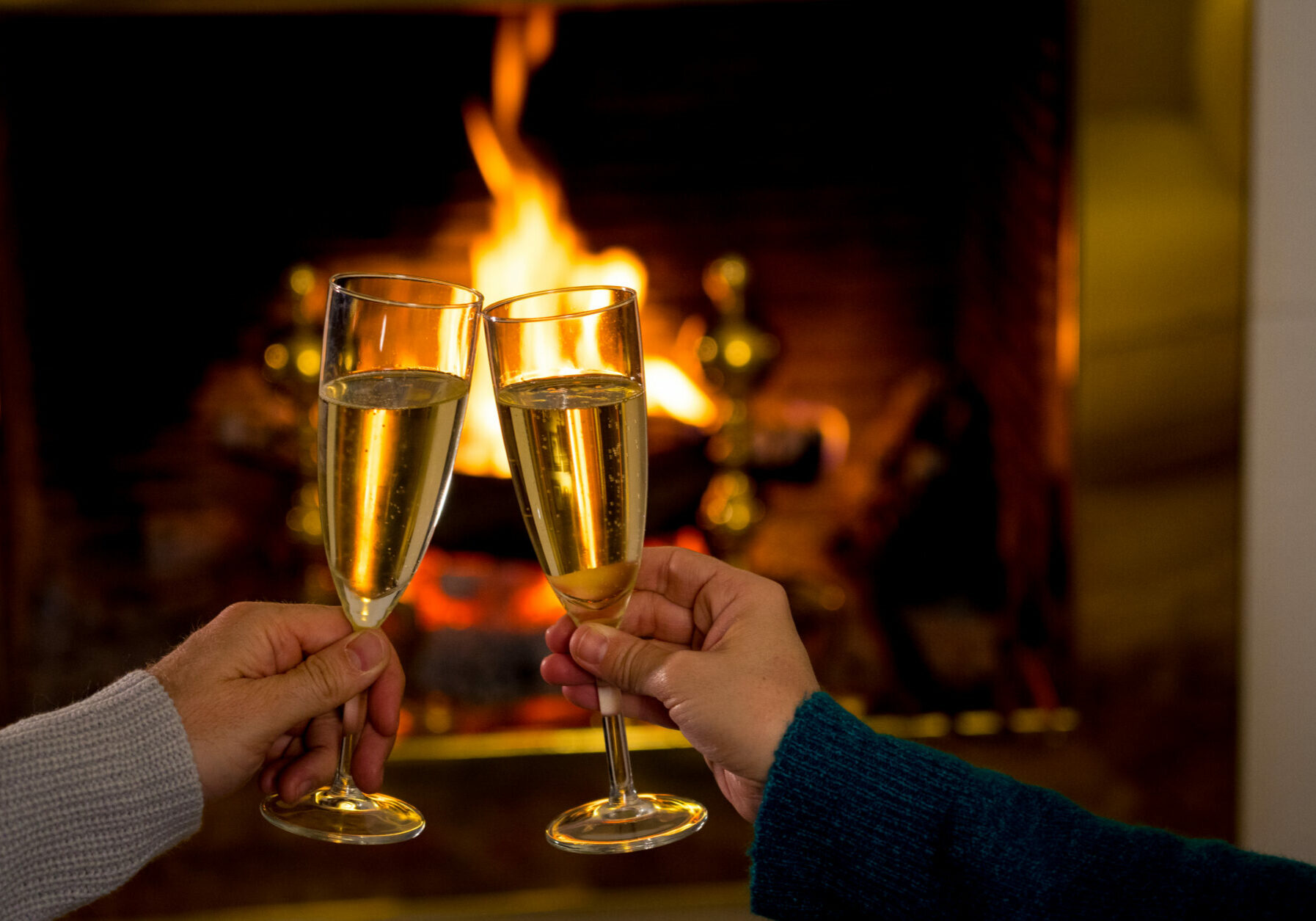 Close up of romantic couple holding two champagne glasses toasting by open wood fireplace celebrating Love happy moments together at cabin in winter holiday vacation and valentines or anniversary.