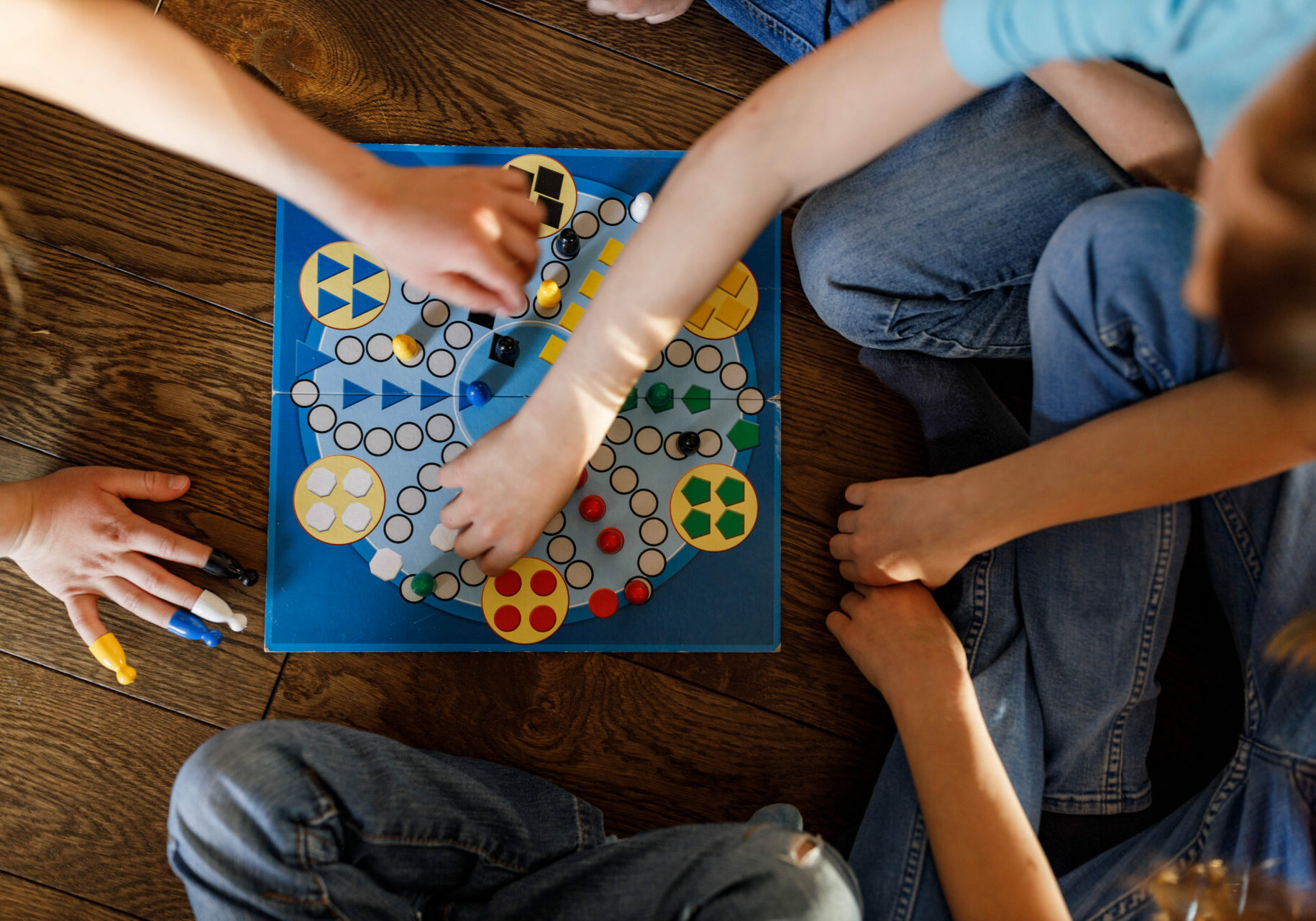 High angle view of unrecognizable kids playing ludo game at home.